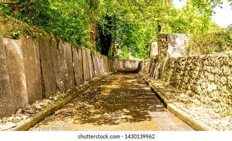 Exterior passageway of Graveyard Abbey with tombstones resting on the walls in the village of Athlone, beautiful sunny spring day in the county of Westmeath, Ireland