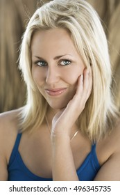 Exterior portrait shot of a happy smiling beautiful blond haired female model with stunning blue eyes.