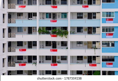Exterior of public housing in heartland neighbourhood; HDB flats painted in white and blue, with Singapore flags hung over the balconies to welcome National Day in August