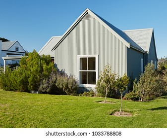 Exterior of the rear facade and large backyard of a contemporary country style home on a sunny day