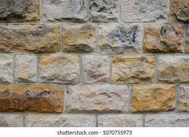 An exterior sandstone wall. You can see the tool marks in the sandstone blocks, where the stonemason has carved out the shape of the blocks.