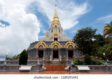 Exterior shot of ancient temple facade with golden spire and green trees in yard called Phra Chedi Boromathat, Mae Salong, Thailand