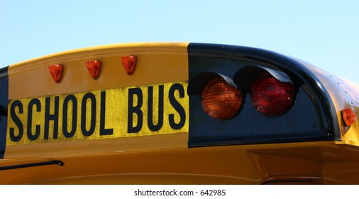 Exterior shot of the back of the school bus, showing lights and the words: school bus in black