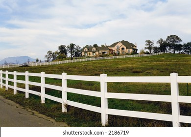 Exterior shot of a large luxurious home on acreage set up for horses.