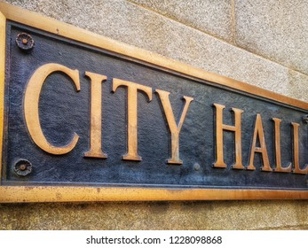 """Exterior sign that reads """"City Hall"""" in brass lettering. Close up. Graphic resource."""