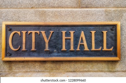 """Exterior sign that reads """"City Hall"""" in brass lettering. Graphic resource."""