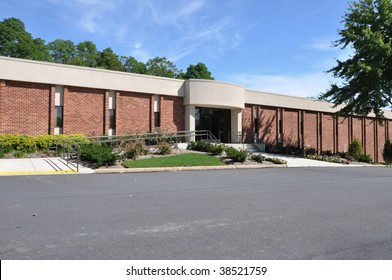 exterior of a small office building with a handicap ramp by a parking lot
