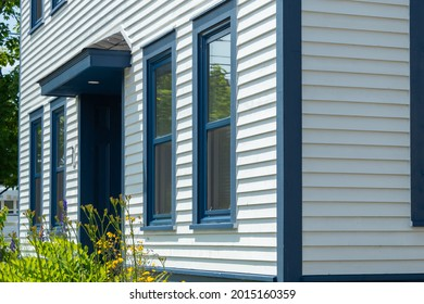The exterior of a stark white cape cod clapboard horizontal wooden board siding wall with multiple blue trim double hung windows. There are vibrant green flowers in front of the vintage windows.