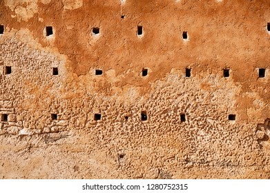 The exterior surrounding wall of the unfinished mosque known as the Tower of Hassan in Rabat, Morocco is pockmarked with square holes that were intended to hold beams of woods for floors.