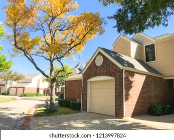 Exterior townhouse complex neighborhood in suburban Dallas-Fort Worth with attached garage. Autumn fall foliage color in Texas, America.