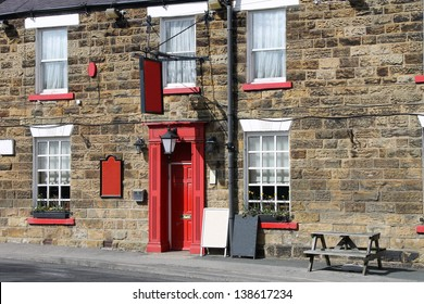 Exterior of traditional English pub in rural countryside.