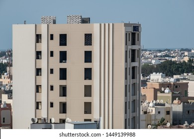 Exterior of two-tone white and cream apartment block under construction against the landscape of an urban Middle Eastern town with villas and palm trees and the sea in the distance.