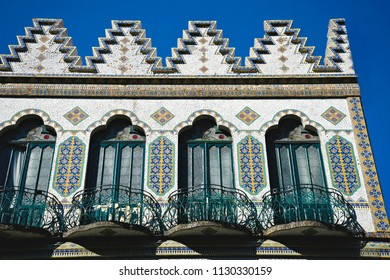 Exterior view of a Colonial building with Talavera tile facade decorations and handcrafted iron balcony railings on the 5 de Mayo in the historic center of Puebla, Mexico.