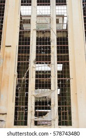 Exterior view of dirty old abandoned vandalised factory ruin, broken window glass rusty steel structure, copy space.