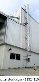 Exterior view, factory building with stairway up to repair on the roof, fire escape stairs.