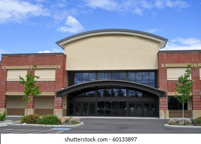 An exterior view of a generic shopping center store building outside in the summer.