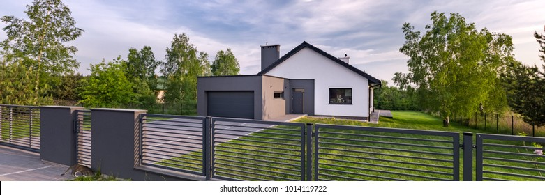 Exterior view of a house with fence and garage, panorama