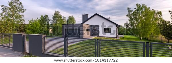 Außenansicht eines Hauses mit Zaun und Garage, Panorama