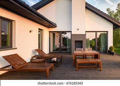 Exterior view of house with patio with wooden furniture