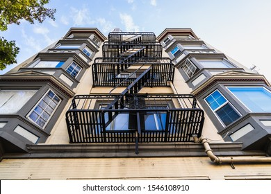 Exterior view of multifamily residential building; Old metal fire escape stairs hanging on side of the building; Berkeley, San Francisco Bay Area, California
