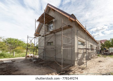 Exterior view of new house under construction and painting. Scaffolding for exterior plastering at home side view