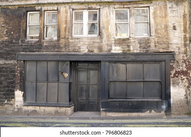 Exterior View of an Old Boarded up Derelict Shop and Residential Building on a City High Street