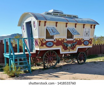 An exterior view of an old circus trailer parked in the California desert