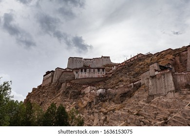 Exterior view of ruin of famous Gyantse Dzong, Gyantse Fortress on a cloudy summer day, located on top of mountain, with colorful prayer flag, Gyantse County, Tibet Autonomous Region, China