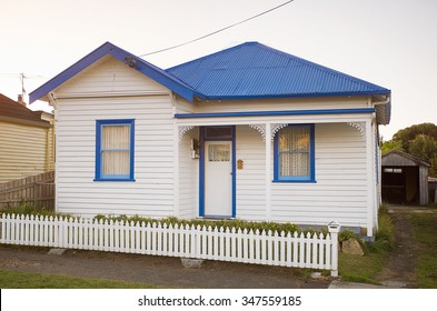 Exterior view of white weatherboard house in suburban street