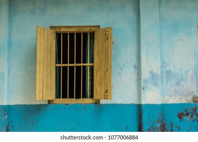 Exterior view of a yellow window with bars and no glass, blue curtains and open yellow shutters in a two-tone blue wall.