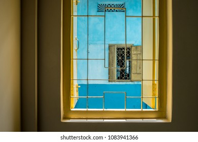 Exterior view of a yellow window with bars and no glass, and open yellow shutters in a two-tone blue wall seen through a window opening in a yellow wall.