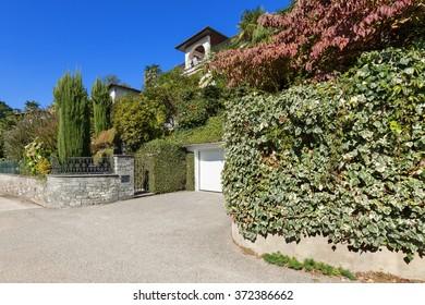 exterior of a villa hidden by a lush garden, garage