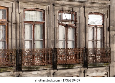 Exterior of a vintage derelict apartment building. Facade of an abandoned historical house in Porto, in need of restoration. False balconies or balconets are common in Portugal.