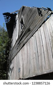 Exterior wall of an antique oaken barn that is slowly deteriorating and falling, in close, tight view.