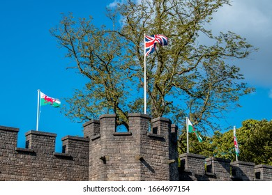Exterior wall of Cardiff Castle, British flag and flags of Wales. Trees in background.