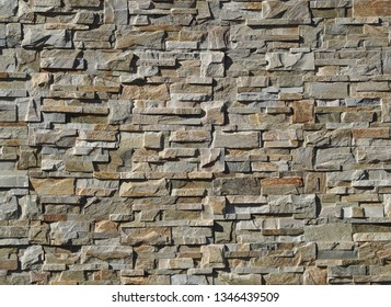Exterior wall cladding made of   natural stones with irregular shapes. Colors are shades of gray and brown