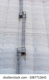 exterior wall of grain storage silo and ladder with platforms ascending to top of silo