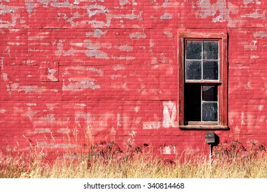 The exterior wall on the side of an old red building with a broken window.