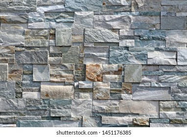 Exterior wall stone cladding made of rocks with different shapes and colors. Background and texture
