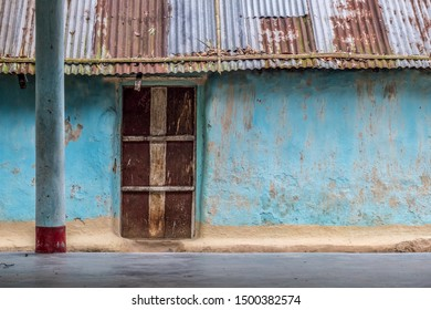 The exterior of a weathered, old, mud house with corrugated iron roof and metal door.