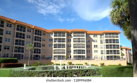 Exterior wide establishing shot of large condominium or apartment building complex courtyard facility during beautiful summer day time in tropical setting
