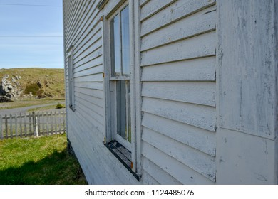 The exterior wooden white wall of a vintage two storey house. The wall has two windows and there's a garden of green grass and a white picket fence. The background has a small rocky hill.