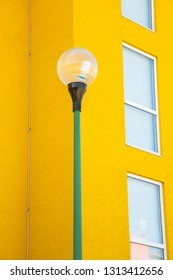 An exterior yard light with a bright yellow building as background