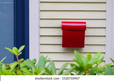The exterior of a yellow clapboard wall of a house with a bright red metal mailbox. The postal container is to the right of a blue door with glass.  There's some green shrubs in the foreground.