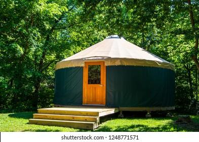 Exterior of yurt in trees daytime