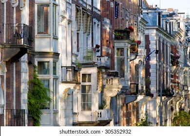 Exteriors of Amsterdam quaint houses along a canal, beautifully iluminated at sunset, leading to a typical image of the dutch capital