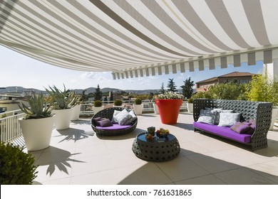 exteriors shots of a modern terrace with awnings and contemporary sofas and armchairs