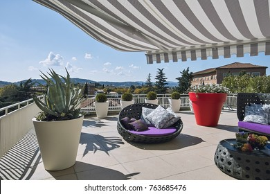 exteriors shots of a modern terrace with awnings and sofas  and armchairs made of wicker in the foreground the big vase with a agave plant