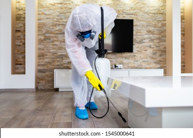 Exterminator in work wear spraying pesticide with sprayer.