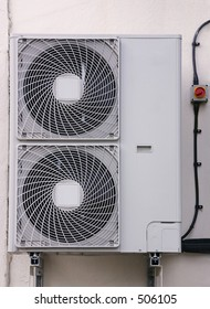 An external air conditioning exhaust unit mounted on a wall.